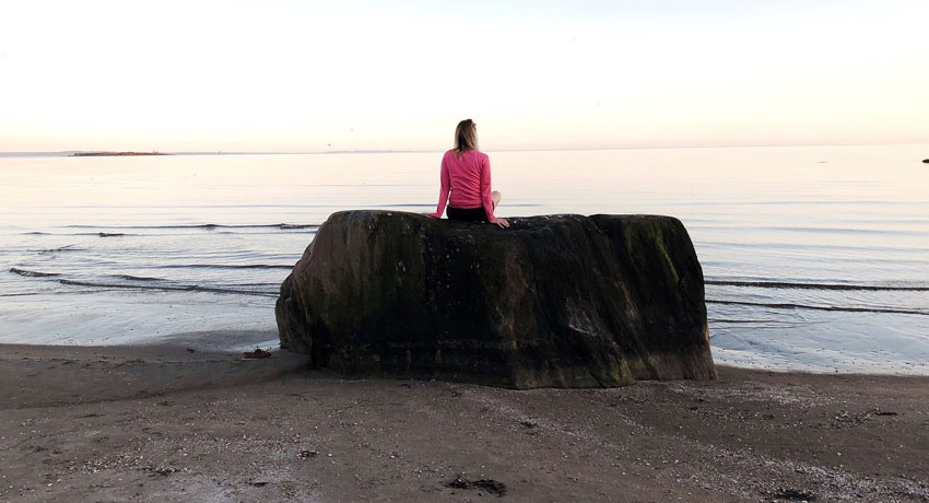 Person sitting on large stone by the sea